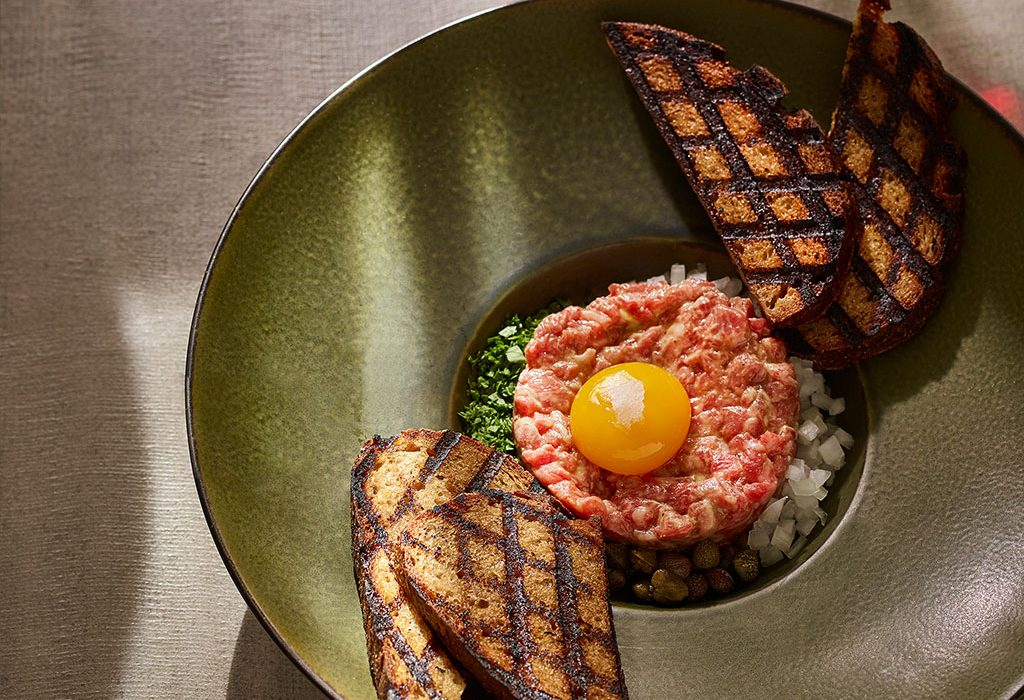 Steak tartare plated with egg and toast